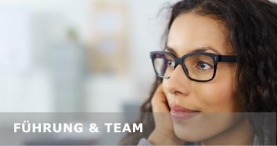 Führung und Team - Junge Frau mit Brille blickt gedanklich nach vorne