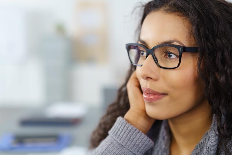 Führung und Team - Junge Frau mit Brille blickt gedanklich in die Zukunft