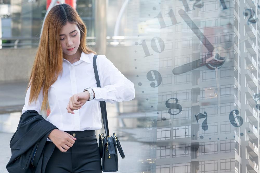 Arbeitszeitberatung - Junge Frau schaut auf ihre Armbanduhr