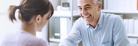 Supportive Leadership - Vorgesetzter spricht lächelnd und verständnisvoll mit Mitarbeiterin