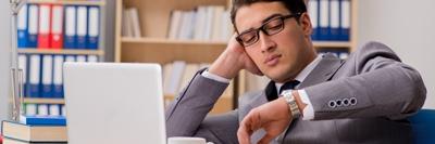 Fehlzeiten reduzieren, Präsentismus überwinden - Junger Mann im Anzug schaut auf die Uhr